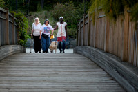 Three women walking across a bridge.  One using a guide dog and one using a white cane.  Women appear very far away,