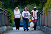 Three women walking across a bridge.  One using a guide dog and one using a white cane.  Women appear very close.