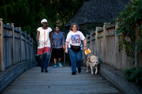 Three women walking across a bridge.  One using a guide dog and one using a white cane.